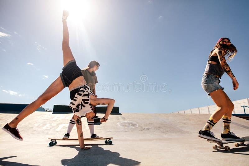 Die Frauen, die Bremsungen am Rochen Skateboard fahren und tun, parken stockbild