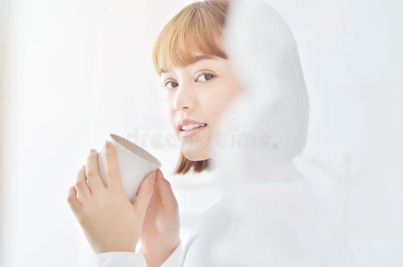 Die Frauen, die ein weißes Hemd tragen, sind lächelnd halten und einen Tasse Kaffee stockbilder