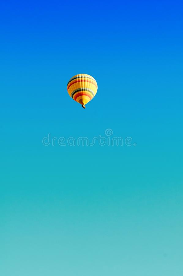 Die Frauen, die Heißluft schauen, steigen über blauem Türkishimmel in Cappadocia die Türkei bei Sonnenaufgang im Ballon auf lizenzfreies stockbild