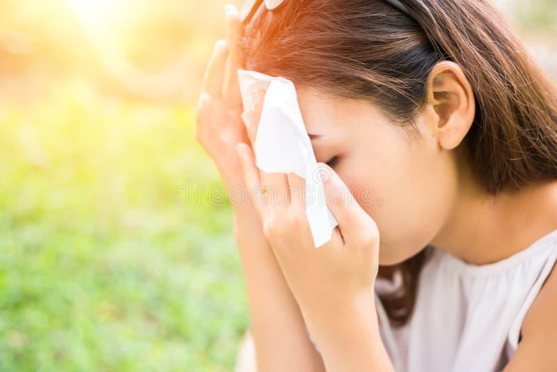 Die Frauen säubern Schweiß auf ihrem Gesicht stockfotografie