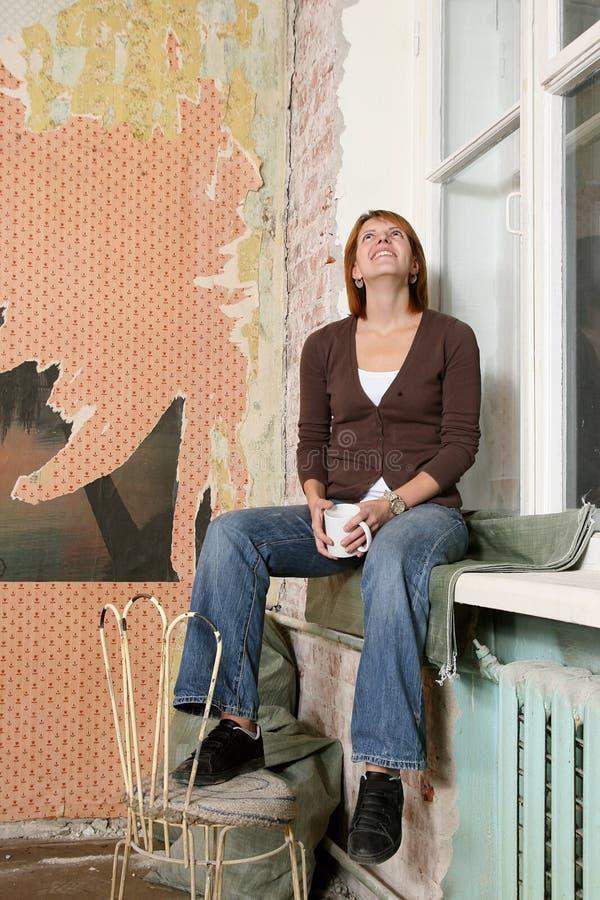 Die Frauen sitzt an einem Fenster mit Schale stockfotografie