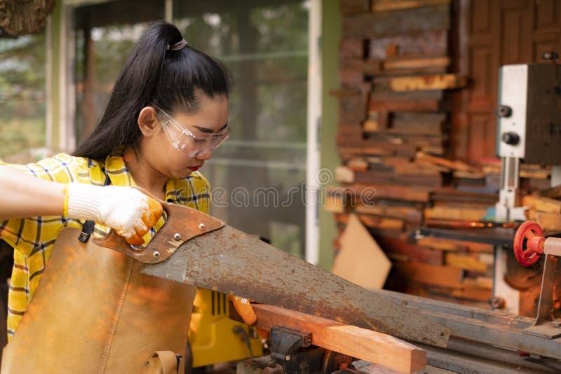Die Frauen-Stellung ist das Handwerk, das geschnittenes Holz an einer Werkbank mit Kreissägeelektrowerkzeugen an der Tischlermasc stockfoto