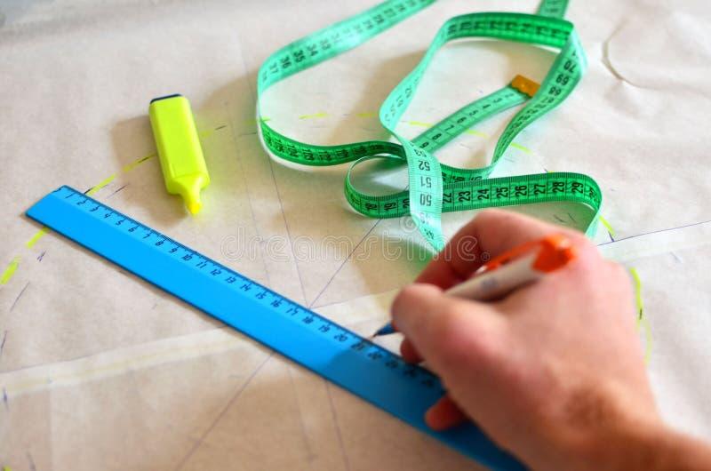 Die Frauendesignerherstellung skizziert Muster, die auf das Gewebe übertragen werden müssen lizenzfreies stockbild