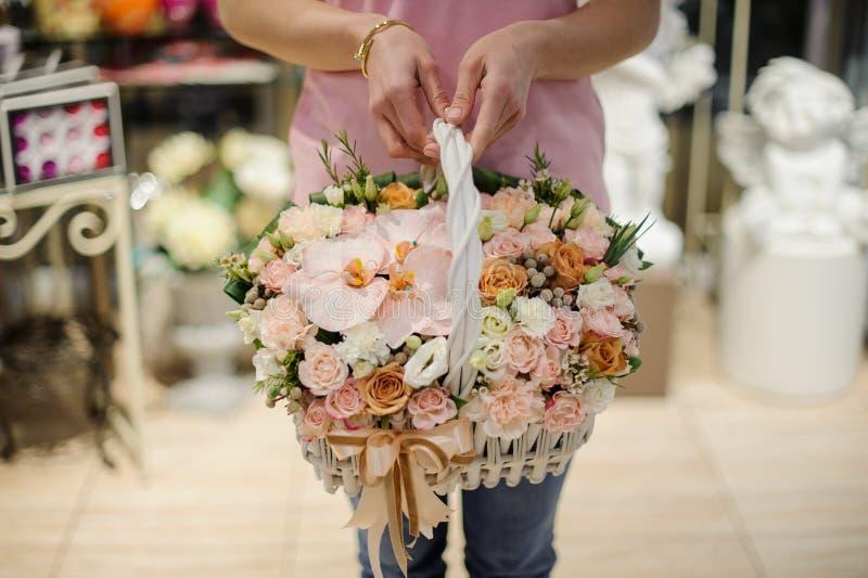 Die Frauenhände, die einen Weidenkorb mit Blumenzusammensetzung in rosa und goldenem Töne Consiting von Rosen und von anderen Blu lizenzfreie stockbilder