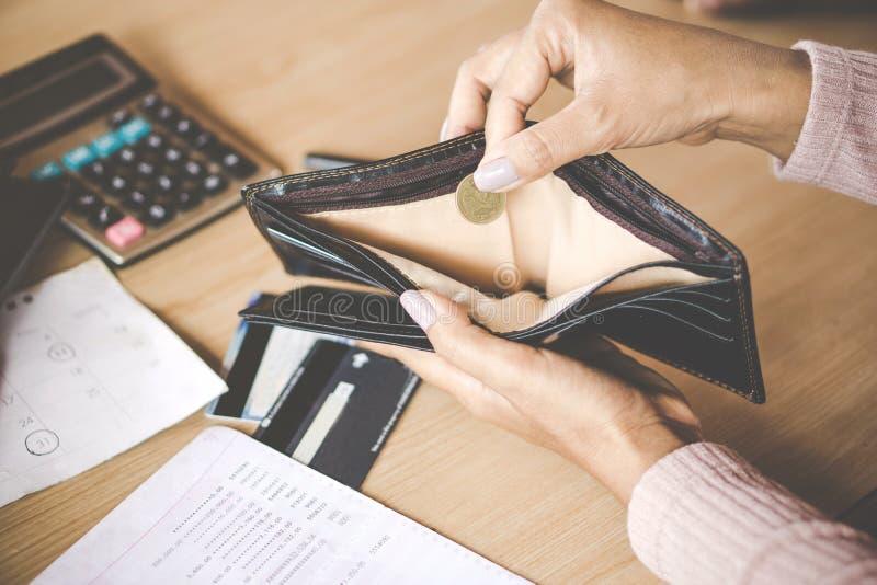 Die Frauenhand, die eine Münze bankrott hält, brach nach Kreditkartezahltag stockfotografie