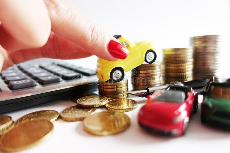 Die Frauenhand, die Spielzeugauto auf Geldmünzen setzt, stapeln das wachsen und schlagen die Zunahme vor, die für Auto gekostet w stockfotografie
