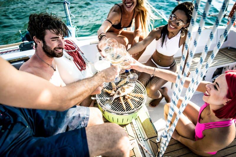 Die Freunde, die Fische machen, grillen auf der Yacht lizenzfreies stockbild