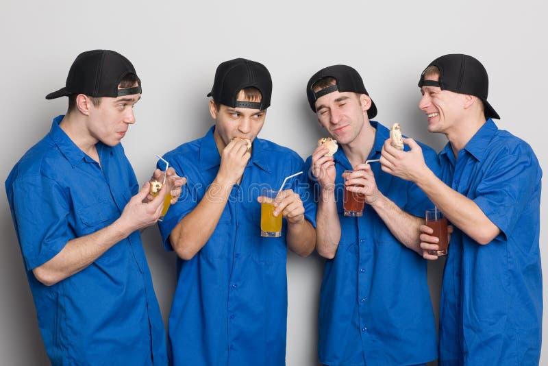 Die Freunde, die Saft trinken und essen Kuchen lizenzfreie stockfotos