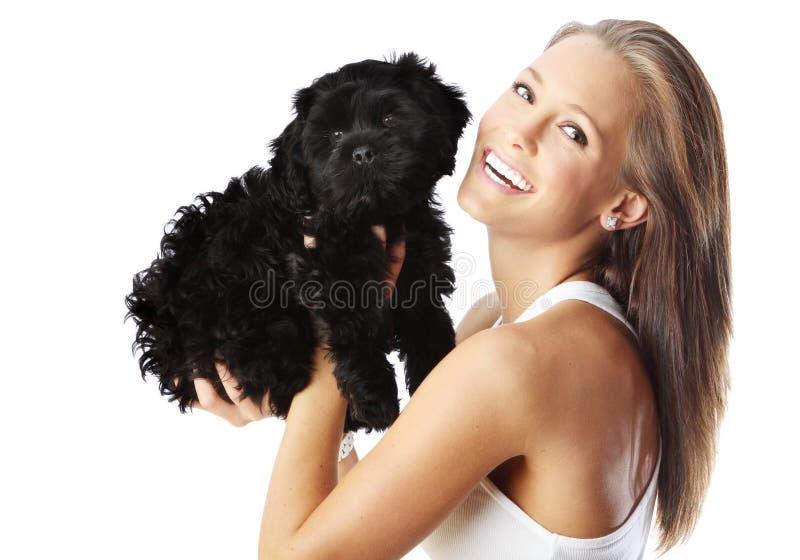 Die freundliche junge Frau, die schwarzen Welpen spielt, trennte stockfoto