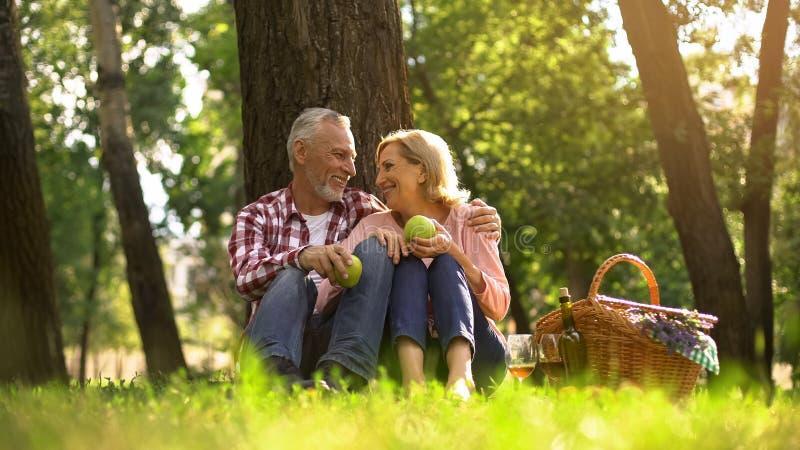 Die frohen gesunden alten auf Gras entspannenden, Äpfel haltenen und umarmenden Paare, picknicken stockfotografie