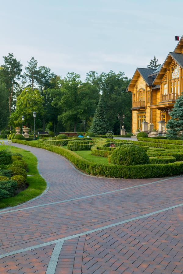 Die Gasse wird mit einem roten Kopfstein in einem gut unterhaltenen Park nahe einem schönen Holzhaus ausgebreitet lizenzfreie stockfotos