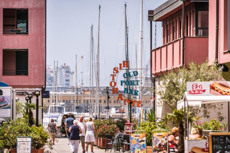Die Gebäude, die Yachten und die gehenden Leute im Hafen von Porto Antico in Genua, Ligurien, Italien, Europa lizenzfreie stockfotos