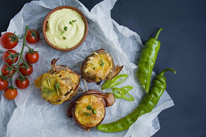 Die gebackenen Frühkartoffeln, die im Speck, auf Spitzenkäse eingewickelt werden, microgreen, Soße und Frischgemüse Dunkler Hinte lizenzfreies stockfoto