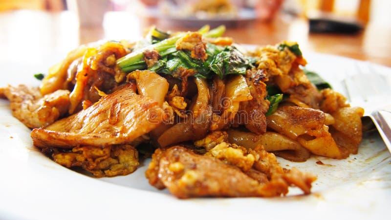 Die gebratene Nudel mit Schweinefleisch im Sojabohnenöl sauced und im Gemüse lizenzfreie stockfotografie