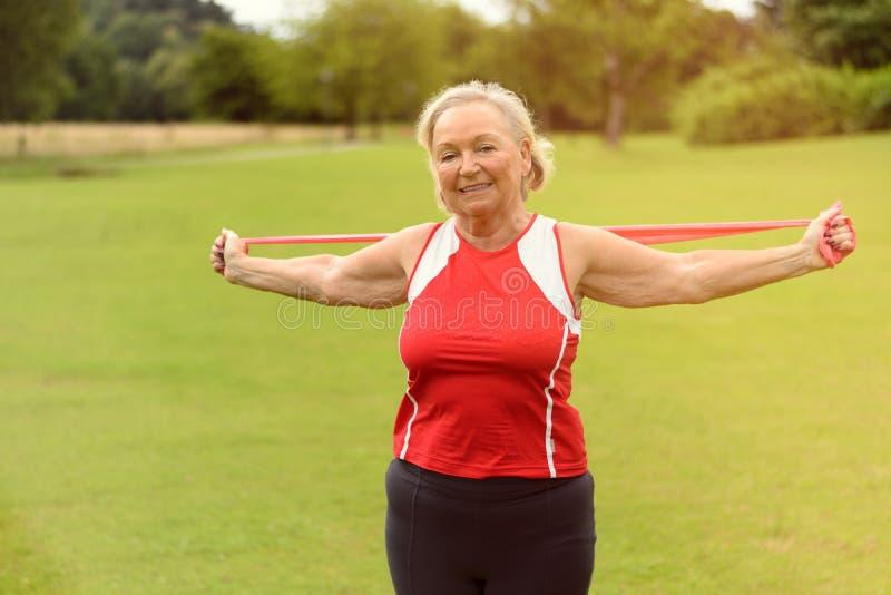 Die geeignete ältere Frau, die Widerstand verwendet, versieht draußen mit einem Band stockfotografie