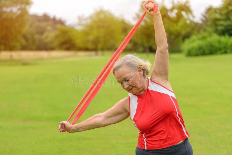 Die geeignete ältere Frau, die Widerstand verwendet, versieht draußen mit einem Band lizenzfreies stockbild