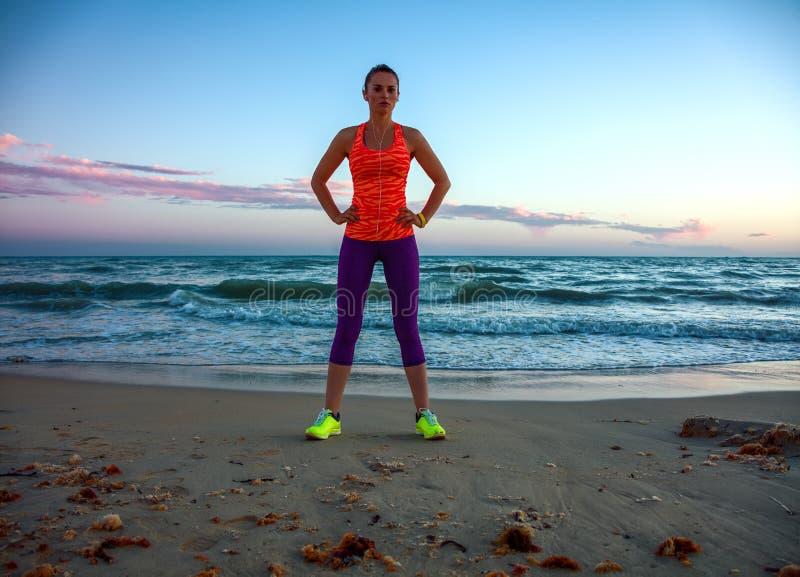 Die geeignete Frau, die im Sport steht, übersetzen auf Strand bei Sonnenuntergang stockfotografie