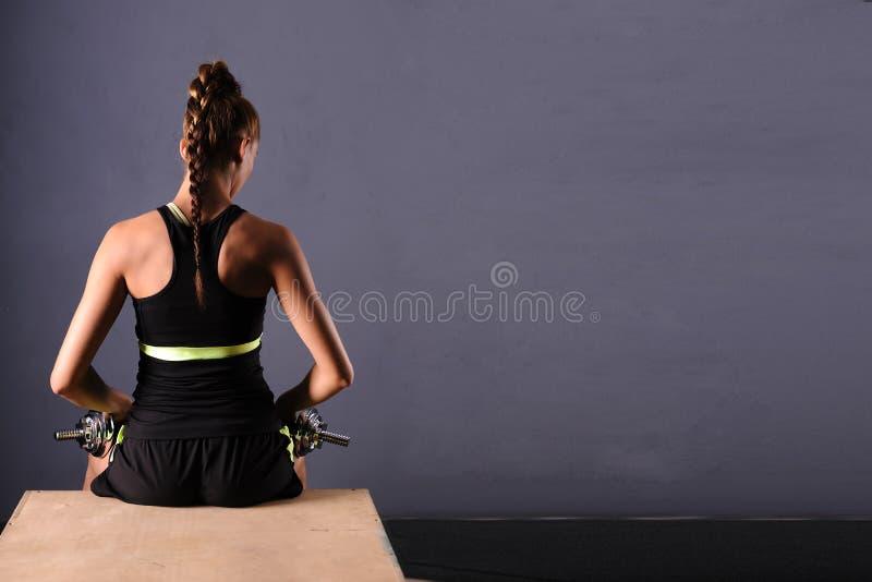 Die geeignete junge Frau, die Schulter tut, hebt mit Dummköpfen, lokalisierter ongray Hintergrund an lizenzfreie stockfotos