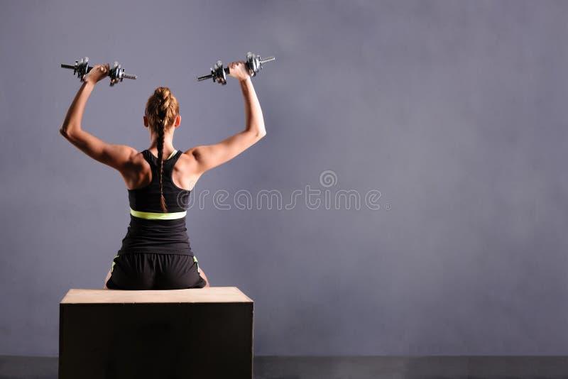 Die geeignete junge Frau, die Schulter tut, hebt mit Dummköpfen, lokalisierter ongray Hintergrund an stockfoto