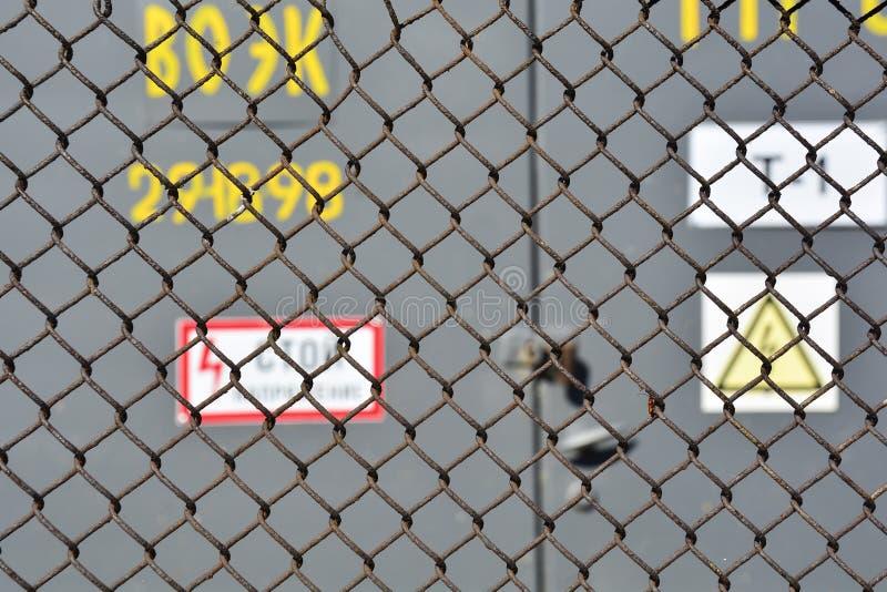 Die Gefahr der Hochspannung Stahlmaschenzaunhochspannungstransformatornebenstelle draußen Weicher Fokus Abstrakter Hintergrund f? stockbild
