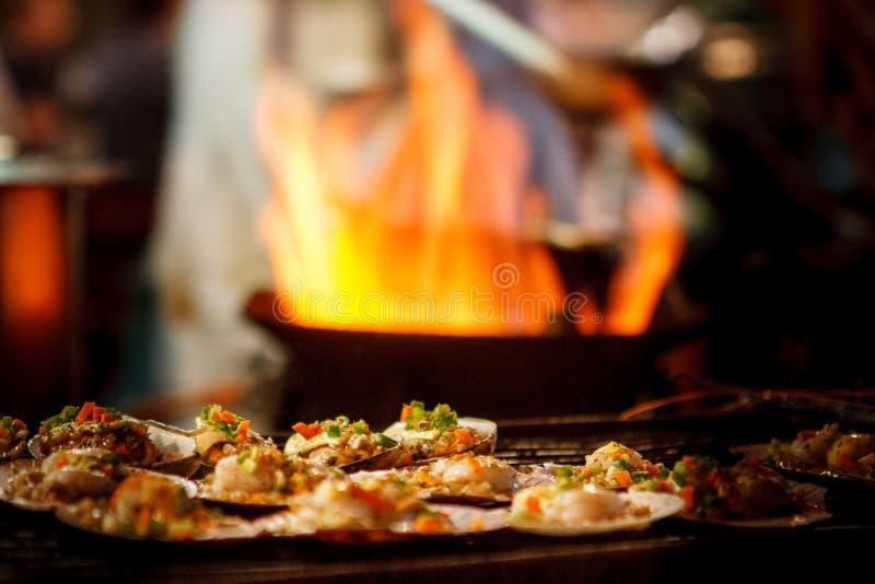 Die gegrillten Kamm-Muscheln, die an einem Straßenmarkt verkauft werden, klemmen mit einer Wanne fest, die mit Flammen auf dem Hi stockbilder