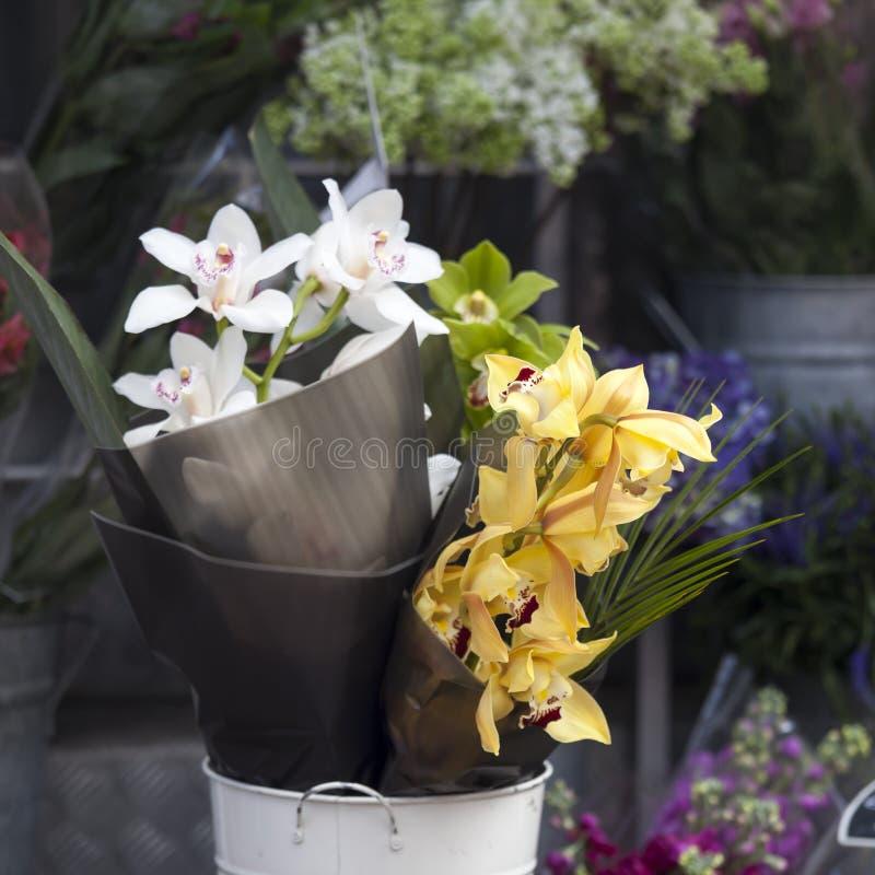 Die Gelb-, weißen und Grünenorchideen in einem weißen Eimer für Verkauf am Eingang zum Speicher stockbilder