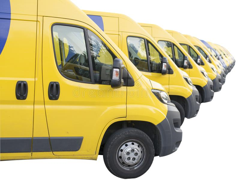 Die gelben Packwagen richteten aus und parkten in einer langen Reihe lokalisiert auf weißem Hintergrund Lieferwagenflotte stockbild