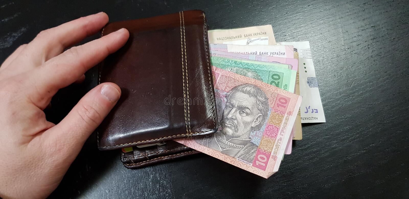 Die Geldbörse, die mit hryvnia Banknoten mit den männlichen Fingern auf ihr voll ist, legen auf schwarze Tabelle lizenzfreies stockfoto
