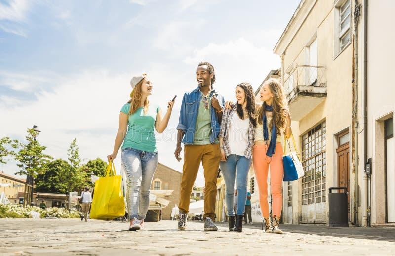 Die gemischtrassigen Freunde gruppieren Haben des Spaßes zusammen gehend auf Stadt lizenzfreie stockfotos