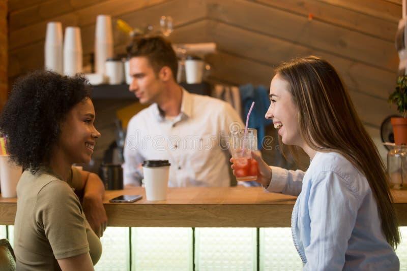 Die gemischtrassigen Freundinnen, die lachen, genießend trinkt am Barzähler stockfoto