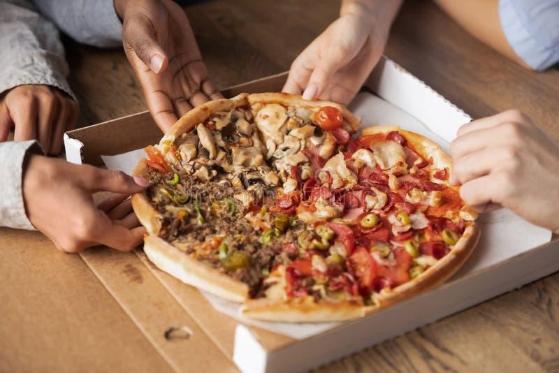 Die gemischtrassigen hungrigen Leute, die Pizzascheibenhände teilen, schließen oben stockfotografie