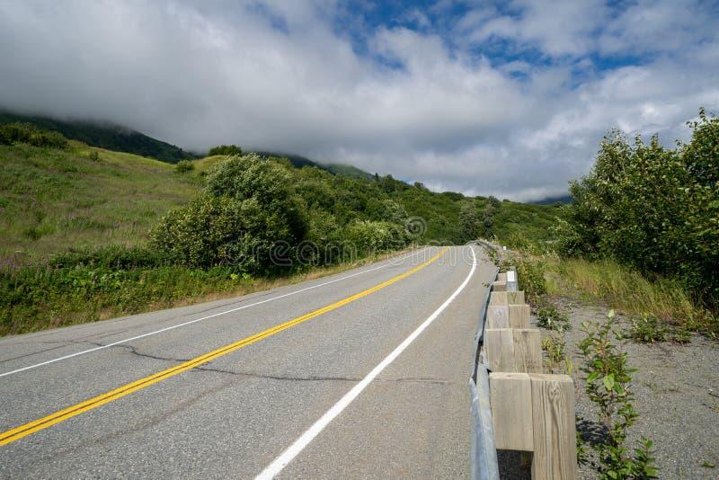 Die gepflasterte Straße zu Hatcher-Durchlauf und die Unabhängigkeit gewinnen nahe Palmer Alaska stockfoto