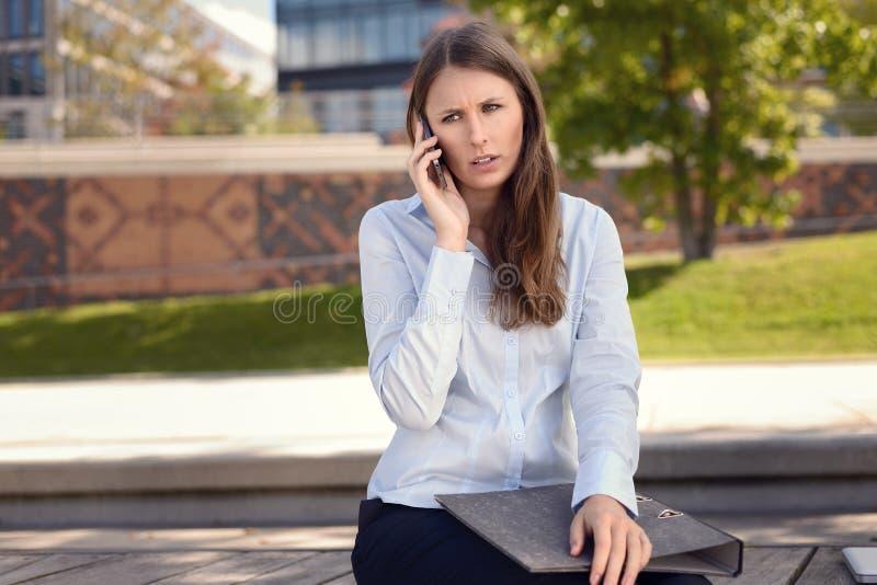 Die gereizte Frau, die als plaudert sie die Stirn runzelt, auf einem Mobile lizenzfreies stockfoto