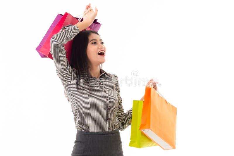 Die Geschäftsfrau, die bunte Einkaufstaschen mit überraschendem Gesichtsausdruck hält lizenzfreie stockfotos
