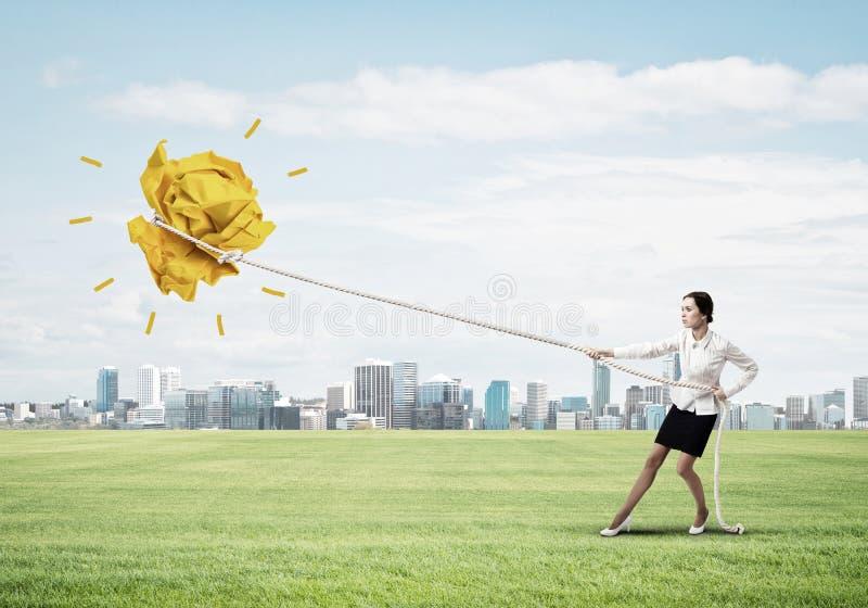 Die Geschäftsfrau, die Papierball mit Seil zieht und ihn macht, heben oben an stockbilder