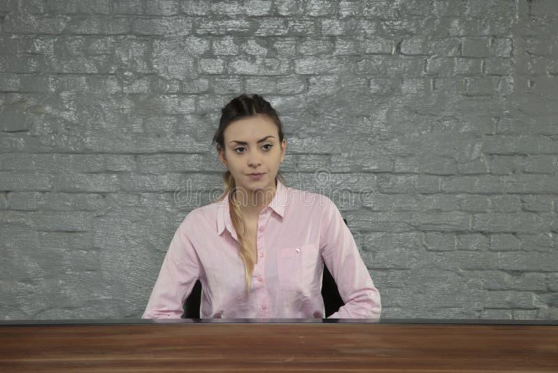 Die Geschäftsfrau, die hinter einem leeren Schreibtisch sitzt, ist er bankrott lizenzfreie stockbilder