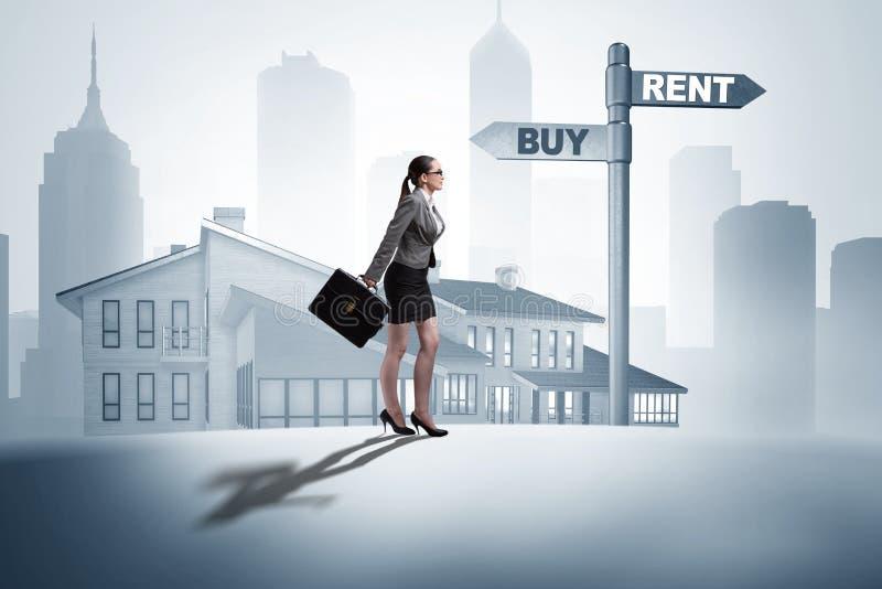 Die Geschäftsfrau an Kreuzungen betweem Kaufen und Mieten stockbild