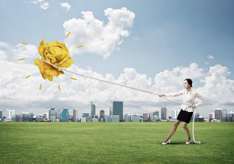 Die Geschäftsfrau, die Papierball mit Seil zieht und ihn macht, heben oben an lizenzfreie stockfotos