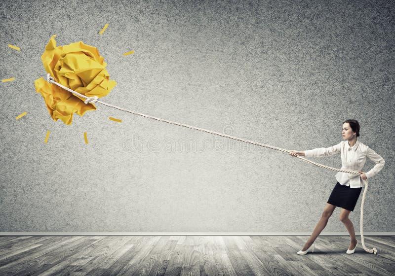Die Geschäftsfrau, die Papierball mit Seil zieht und ihn macht, heben oben an stockfotografie