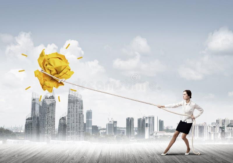 Die Geschäftsfrau, die Papierball mit Seil zieht und ihn macht, heben oben an stockfoto