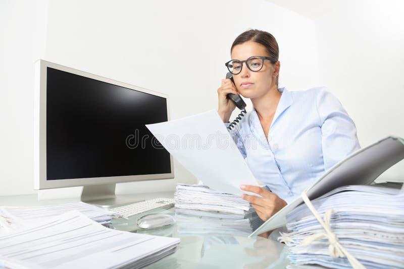 Die Geschäftsfrau, die am Schreibtisch mit Computer arbeitet, liest ein docu stockbild