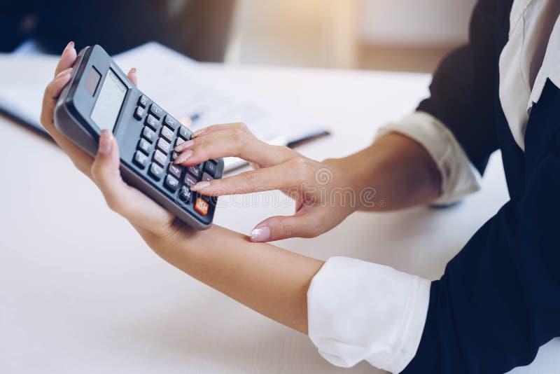 Die Geschäftsfrau, die Taschenrechner für hält, berechnen Zahl und Diskus stockfotos
