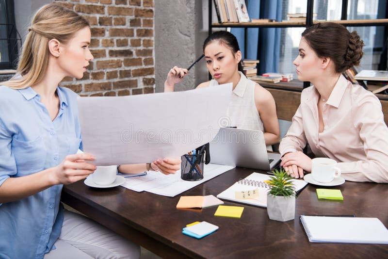 Die Geschäftsfrauen, die Geschäft darstellen, projektieren zu ihrem modernen Büro der multikulturellen Kollegen lizenzfreie stockbilder