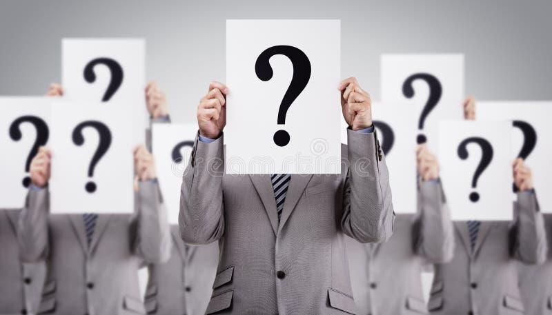 Die Geschäftskollegen, die Fragezeichen halten, unterzeichnet vor thei stockbilder