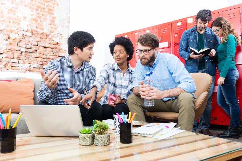 Die Geschäftsleute, die verschiedene Mischung des kreativen Büros des Sofas sitzen, laufen lizenzfreies stockbild