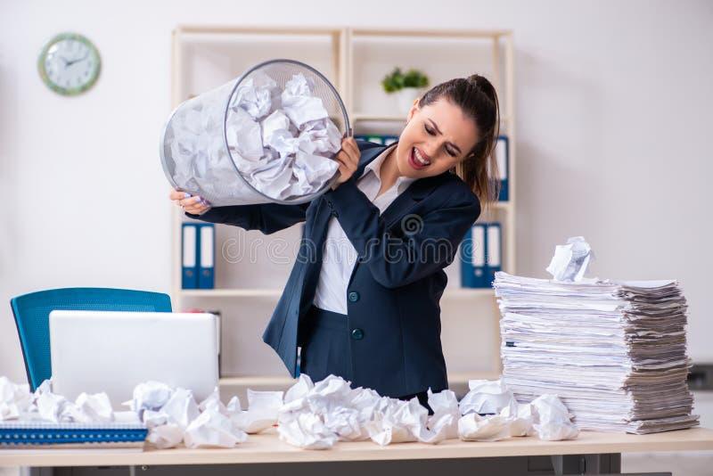 Die Gesch?ftsfrau, die neue Ideen mit vielen Papieren zur?ckweist stockfotografie