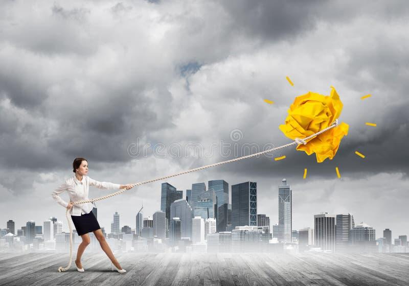 Die Gesch?ftsfrau, die Papierball mit Seil zieht und ihn macht, heben oben an lizenzfreie stockfotografie