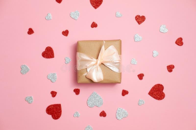 Die Geschenkbox, die im Kraftpapier mit Bandbogen und rotem und grauem Herzen verpackt wurde, formte Valentinsgrüße, die Karte au stockfotos