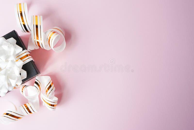 Die Geschenkbox, die in weißem und im Gold eingewickelt wurde, streifte Band auf rosa Pastellhintergrund Leere Anmerkung vorbei g lizenzfreie stockbilder