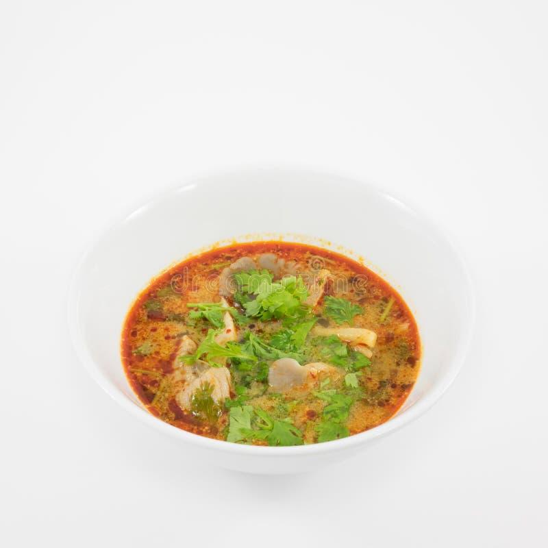 Die geschmackvolle würzige Schweinefleischtom-yum Suppe (heiße und saure Suppe) in der weißen keramischen Schüssel lizenzfreie stockfotografie